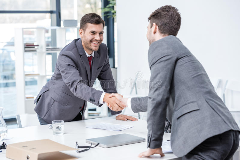 Two smiling businessmen shaking hands at meeting in office. Business concept stock images
