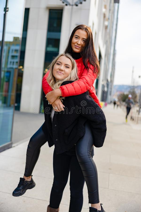Smiling Female Friends Having Fun and Piggybacking In City Environment royalty free stock photo