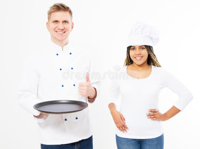 Two smiling chefs in kitchen mock up, chef hold empty tray smiling and show like sign royalty free stock images