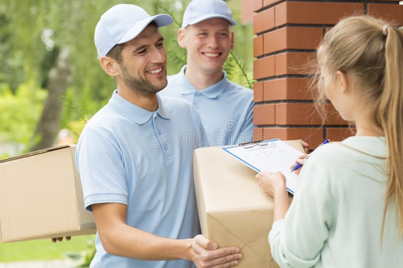 Smiling couriers in blue uniforms and young women filling up delivery documents. Two smiling couriers in blue uniforms and young women filling up delivery royalty free stock photo