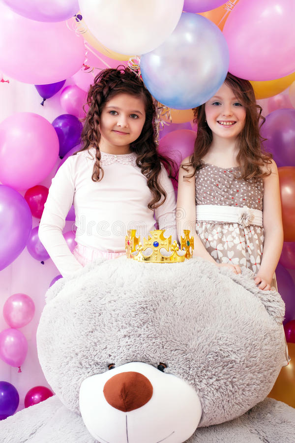 Two smiling cute sisters and big teddy bear. Portrait of two smiling cute sisters and big teddy bear royalty free stock photography