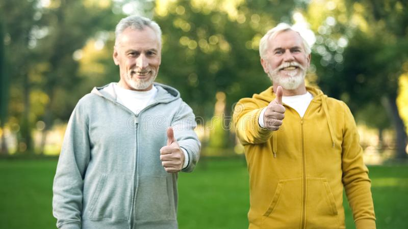 Two smiling elderly men in sportswear showing thumbs up, healthy lifestyle. Stock photo stock images