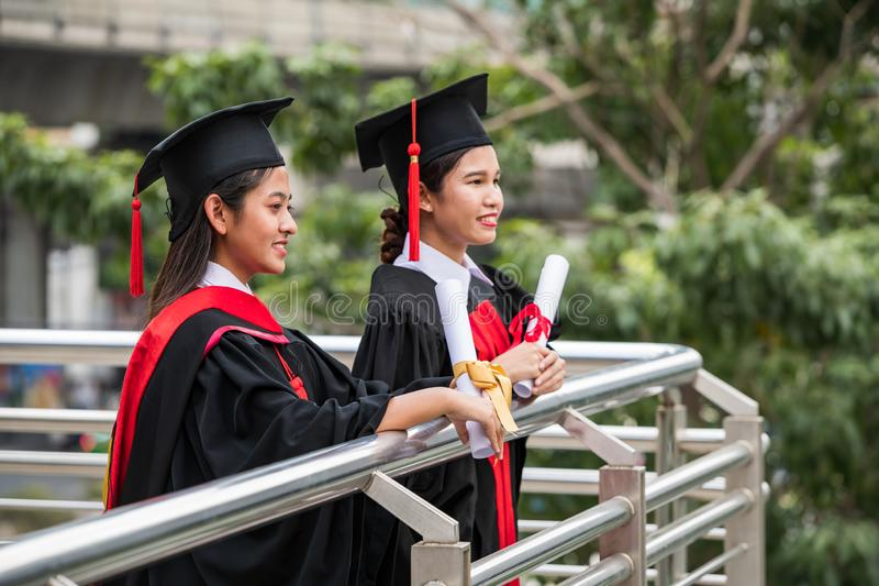 Two smiling female Asian students in graduation gown. Holding the diplomas with eyes looking forward royalty free stock photo