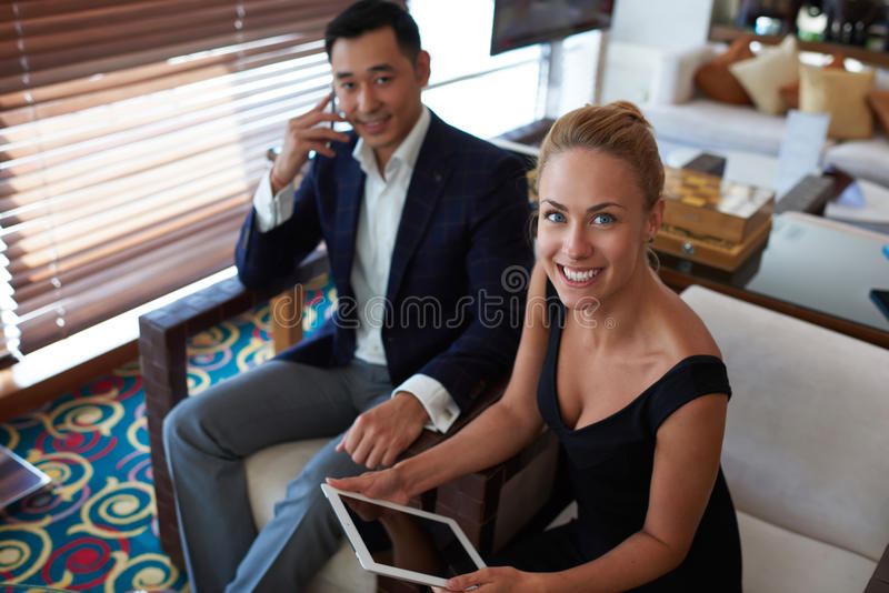 Two smiling financiers dressed in corporate clothes having negotiation while sitting in modern office interior. Businessman talking on mobile phone while his royalty free stock image