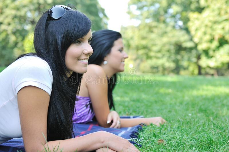 Download Two Smiling Friends Lying Outdoors Stock Image - Image of park, caucasian: 14722891