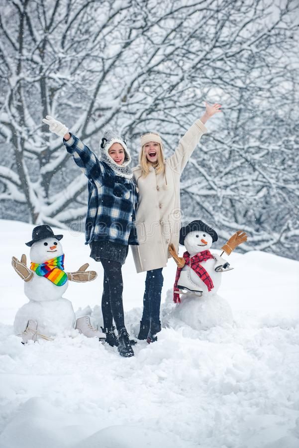 Two smiling friends make Snowman on Christmas background. Making snowman and winter fun for girl. Funny Santa girl stock image