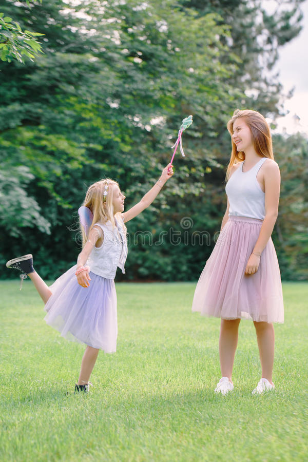 Two smiling funny Caucasian girls sisters wearing pink tutu tulle skirts in park forest meadow at sunset. Friends having fun royalty free stock images