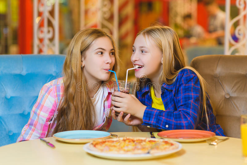 Two smiling girls eating pizza and drinking juice indoor royalty free stock photography