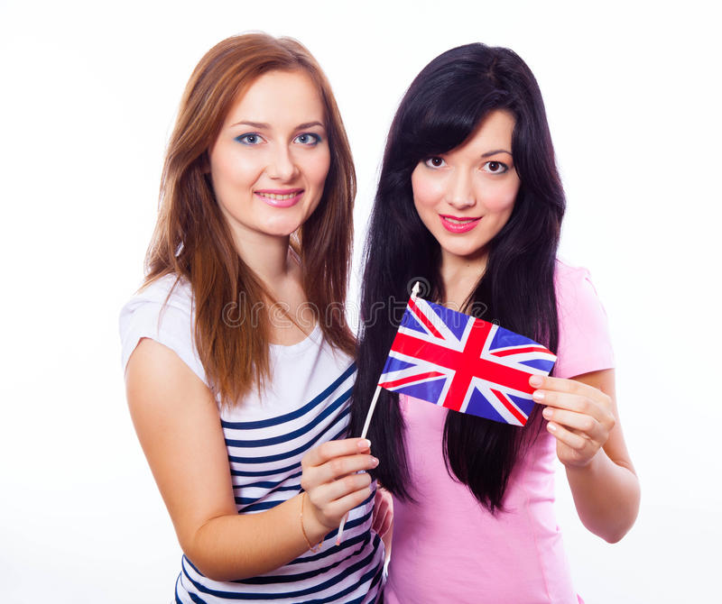 Two smiling girls holding British flag. stock photo