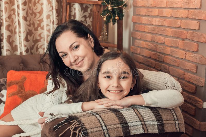 Two smiling girls, mother and daughter siting on a sofa in Chris royalty free stock photo