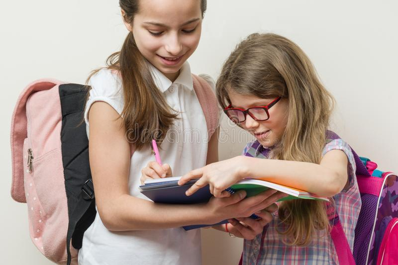 Two smiling girls with school bags. Schoolgirls 7 and 10 years old talking at school. Little girl writes in a notebook royalty free stock image