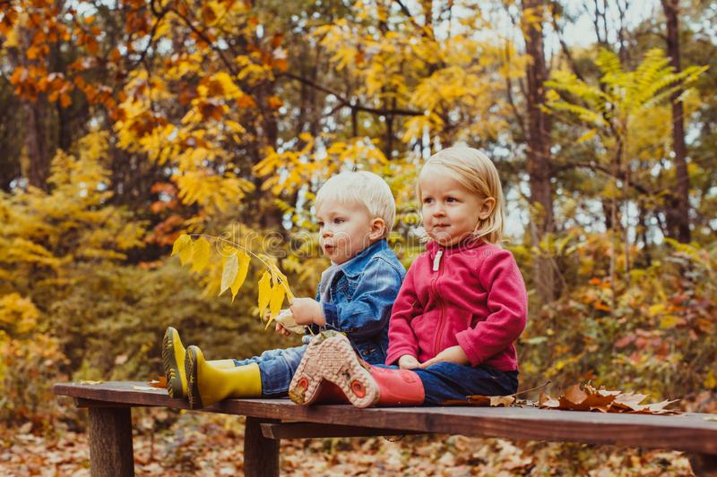 Two smiling happy kids friends, boy and girl sitting on the bench stock images