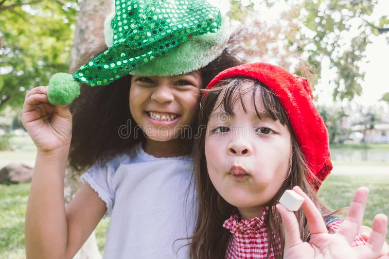 Two smiling happy little girl wear party hat eat candy stock photos