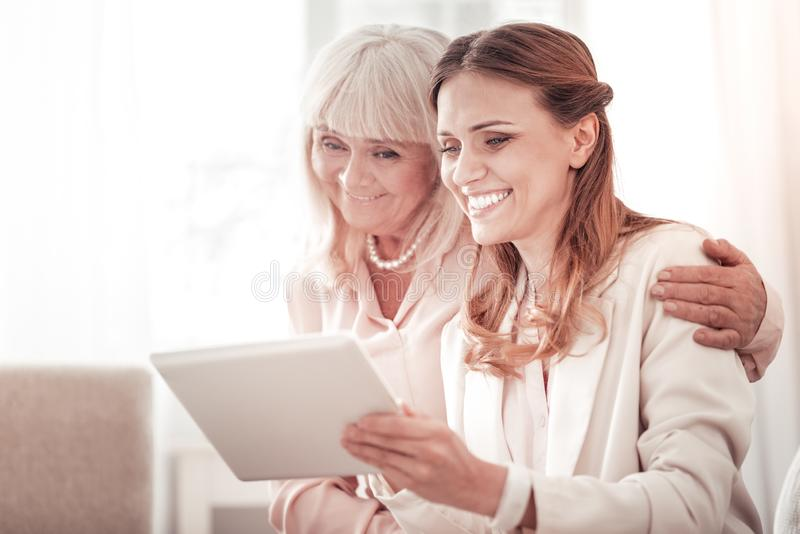 Two smiling happy women looking through the family pictures on a tablet stock image