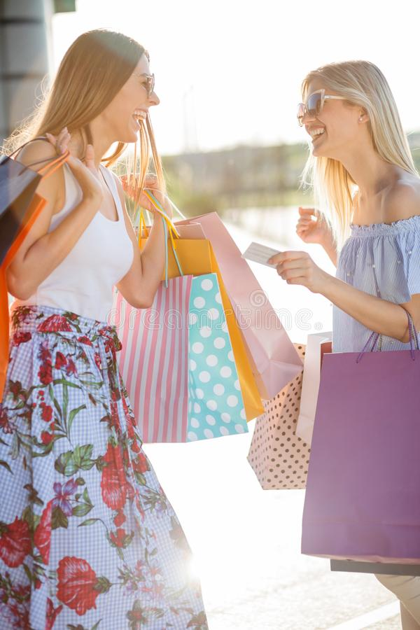 Two smiling happy young women returning from shopping royalty free stock image