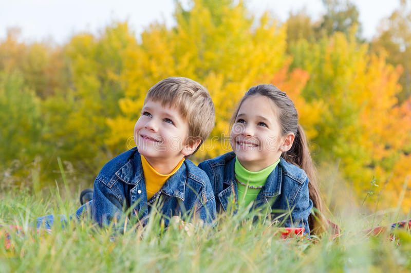 Two smiling kids on the autumn meadow royalty free stock photography