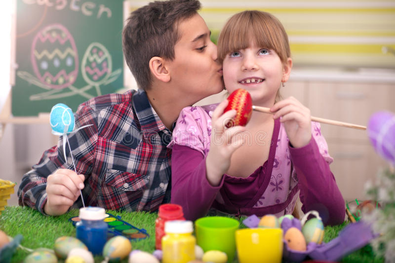 Two smiling kids paint easter eggs. Happy young boy and girl playing with Easter eggs stock images