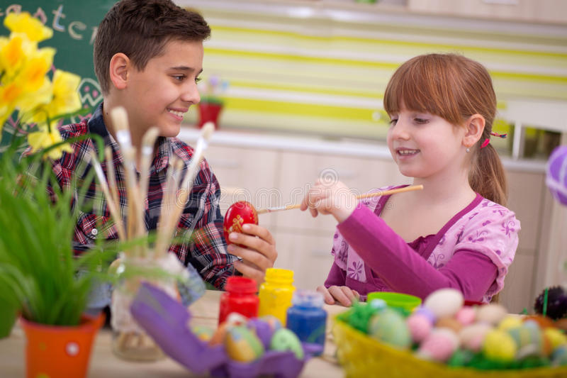 Two smiling kids paint easter eggs. Happy young boy and girl playing with Easter eggs royalty free stock photo