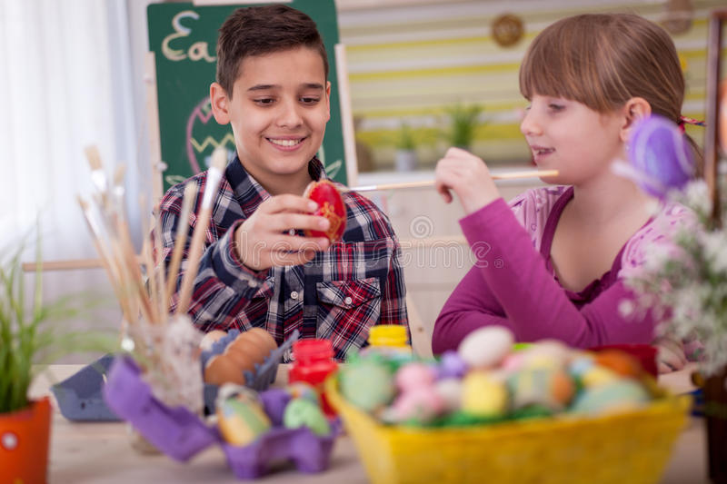 Two smiling kids paint easter eggs. Happy young boy and girl playing with Easter eggs stock image