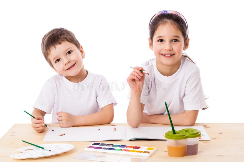 Two smiling kids draws with watercolor together stock image