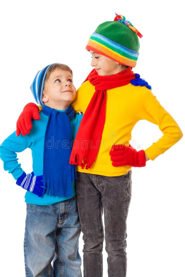 Two smiling kids in winter clothes standing together stock photos