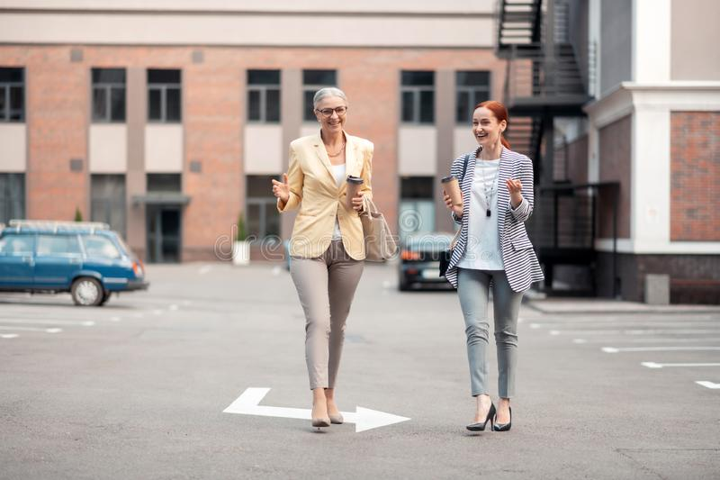 Stylish smiling ladies with paper cups of coffee royalty free stock image