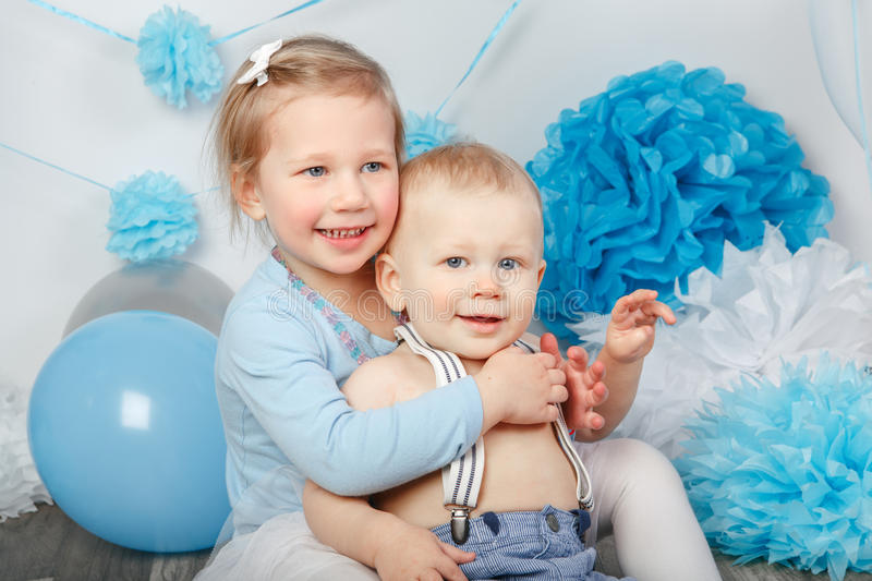 Two smiling laughing hugging cute adorable Caucasian children, toddler girl and baby boy, celebrating birthday. Portrait of two smiling laughing hugging cute stock photography