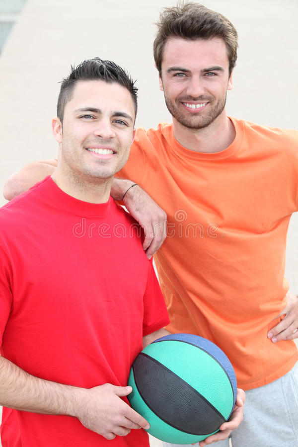 Two smiling men with basket ball. Portrait of two smiling men with basket ball royalty free stock photo