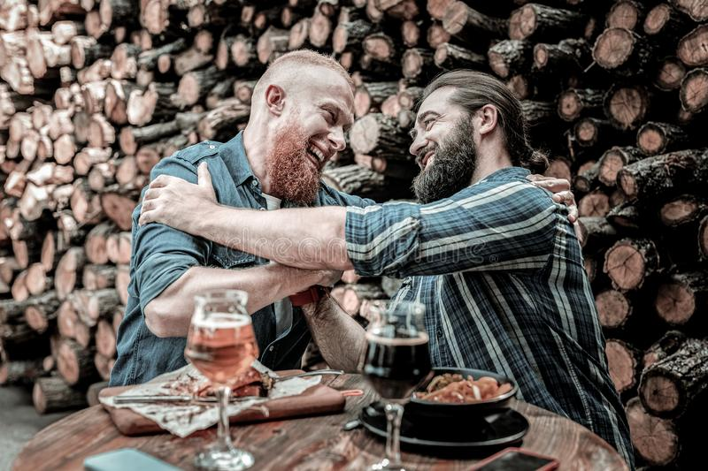Two smiling men giving each other a friendly hug. Best friends. Two happily smiling bearded men sitting in front of fire wood in pub and giving each other a stock images