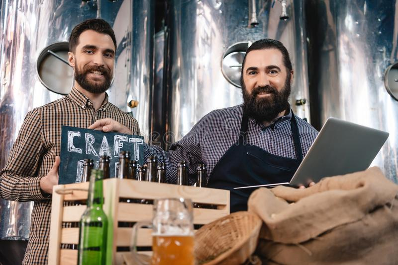 Two smiling men show sign where craft beer is written. Production of craft beer. Process of beer manufacturing. Brewery. Beer crafting stock photos