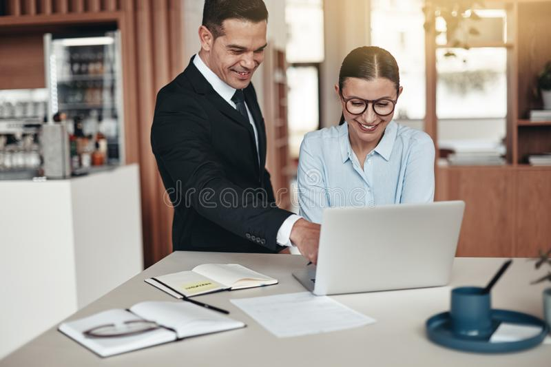 Two smiling office colleagues working together on a laptop stock image