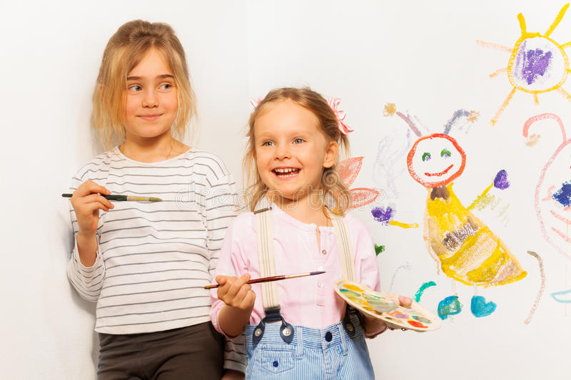 Two smiling painters drawing funny picture royalty free stock image