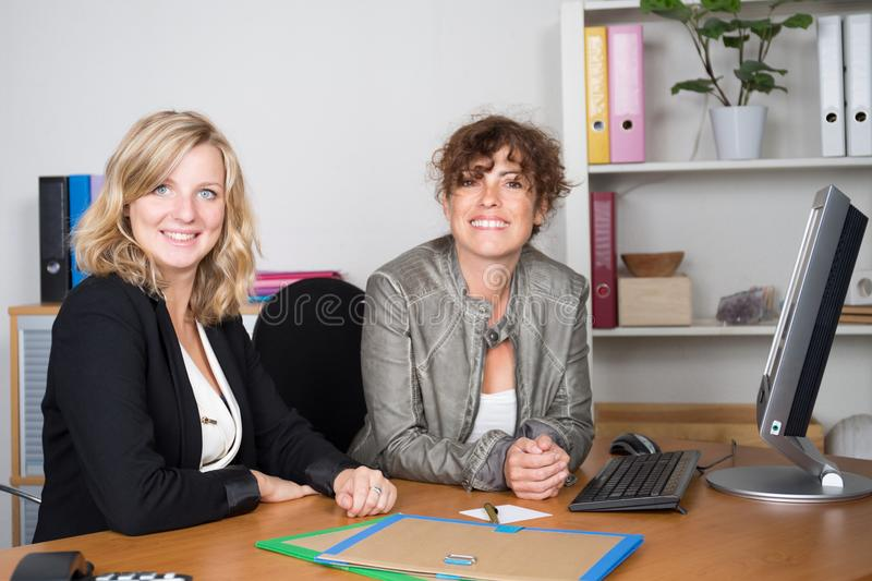 two smiling pretty young business women in corporate team work sitting on workplace stock photos