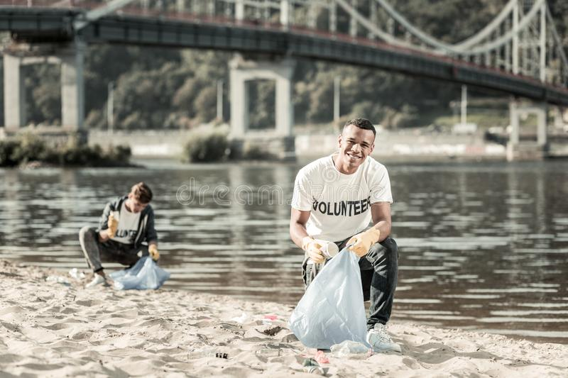 Two smiling responsible students cleaning up trash left behind on the beach. Cleaning up trash. Two smiling responsible students feeling cheerful while cleaning royalty free stock photography