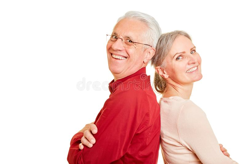 Two smiling seniors as a couple. Two smiling seniors as a happy couple lean against each other stock image