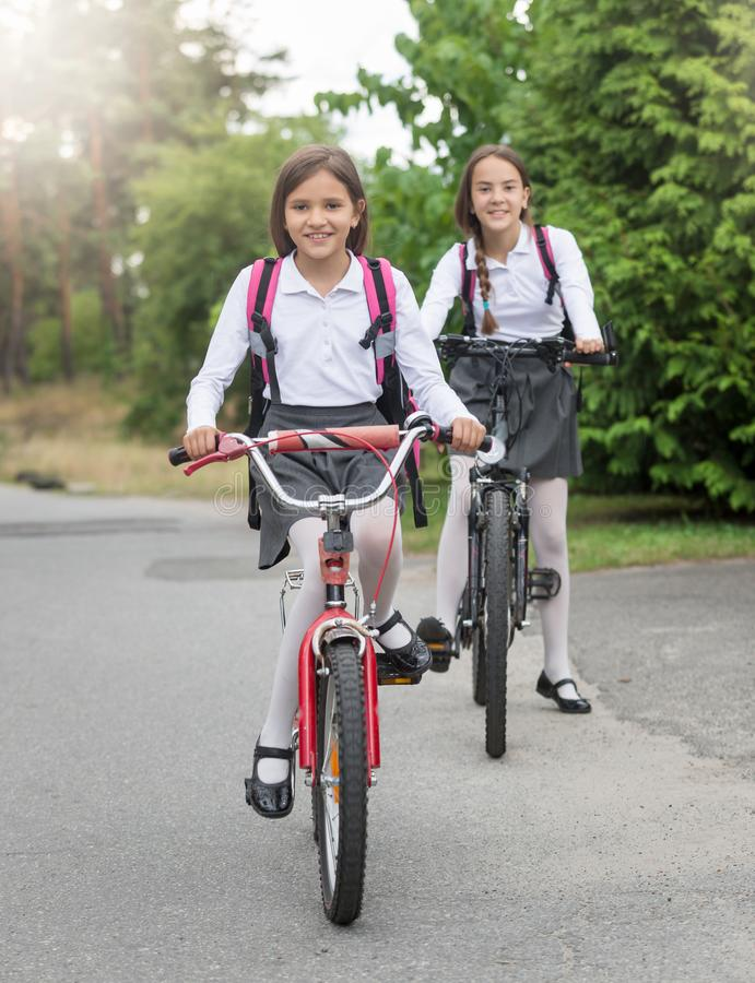 Two smiling sisters riding to school on bicycles. Two smiling sisters with backpacks riding to school on bicycles royalty free stock photos