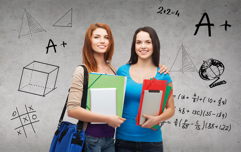 Two smiling students with bag, folders and tablet. Education, technology and people concept - two smiling students with bag, folders and tablet pc standing stock image