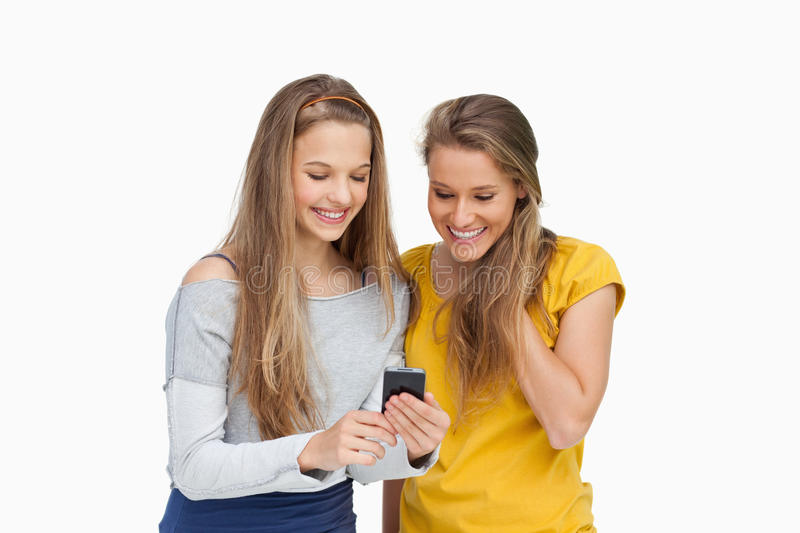 Download Two Smiling Students Looking A Cellphone Screen Stock Photo - Image: 25335340