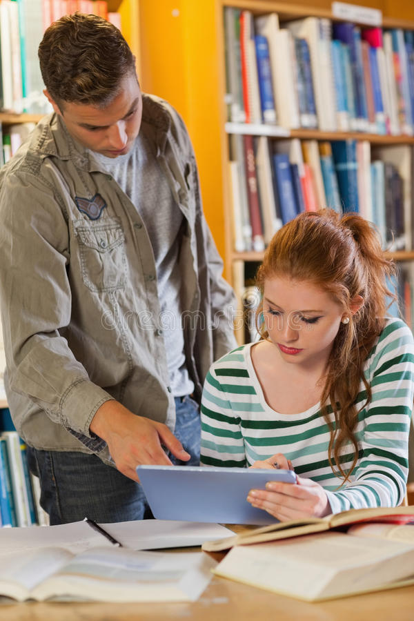 Two smiling students studying together using tablet