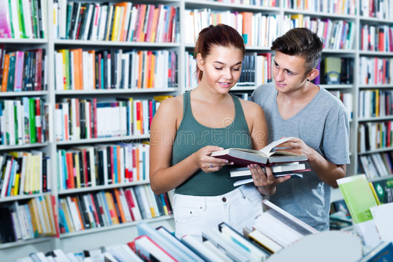 Two smiling teenagers reading book together stock photo