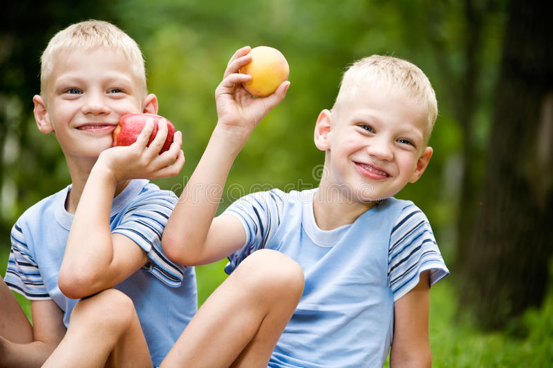 Two smiling twin brothers holding fruits royalty free stock photography