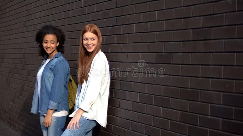 Two smiling university students leaning brick wall, leisure time college campus stock photo