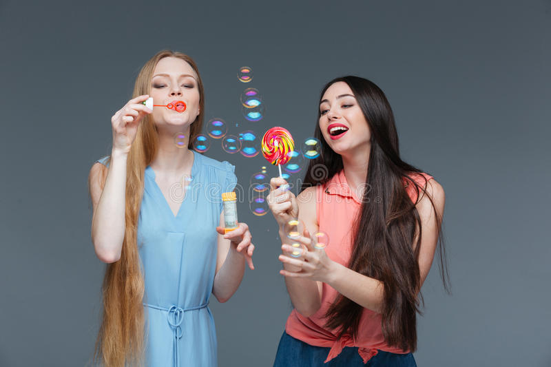 Two smiling women with colorful lollipop standing and blowing bubbles stock photo