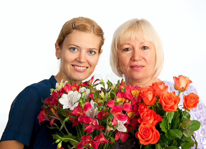 Two Smiling Women With Flowers On White Background Stock Photo