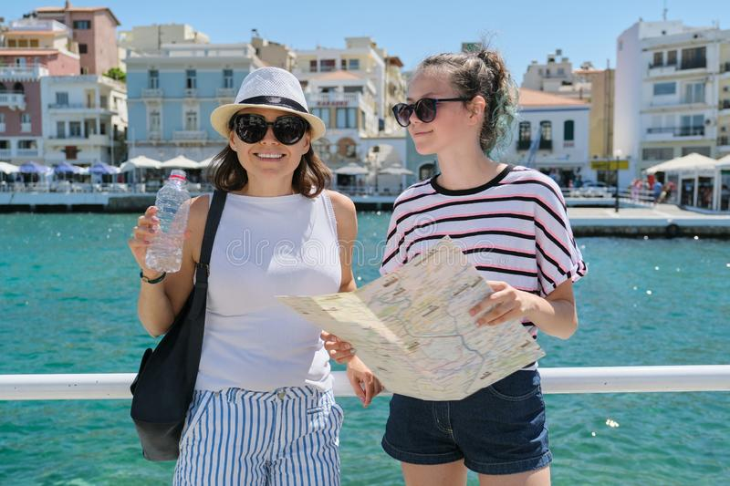 Two smiling women mother and teenager daughter with map on shore of sea bay royalty free stock photography