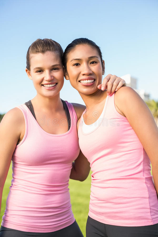 Two smiling women wearing pink for breast cancer. Portrait of two smiling women wearing pink for breast cancer in parkland stock images
