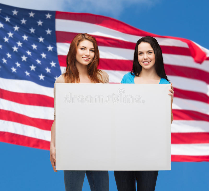 Two smiling young girls with blank white board stock photos