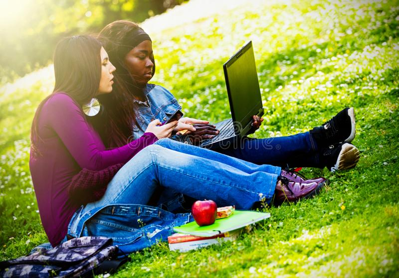 Two smiling young girls using laptop at the park stock photography