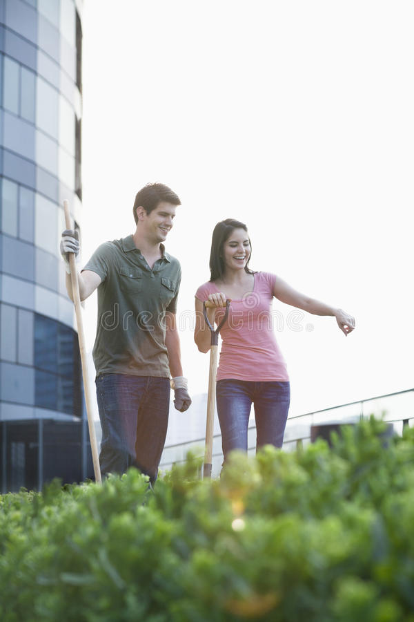 Two smiling young people gardening and pointing at plants in a roof top garden in the city