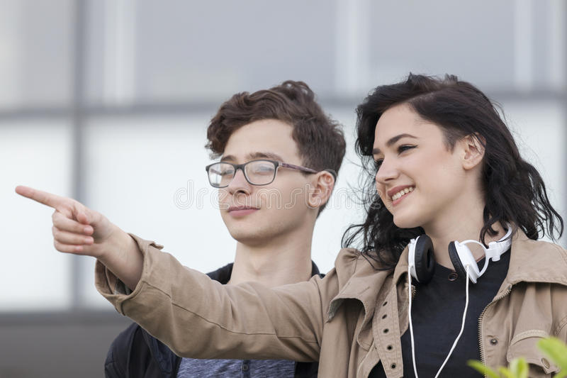 Two smiling young teenage boy and girl planning to look around a royalty free stock images